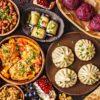 Traditional Georgian cuisine background. Khinkali, phali, chahokhbili, lobio, cheese, eggplant rolls, dark background.